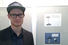 Steffen vor seinen ausgestellten Cartoons